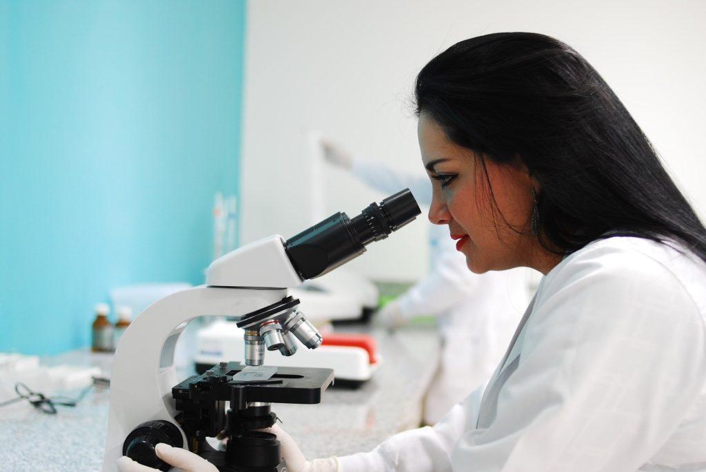 femme regadans dans un microscope