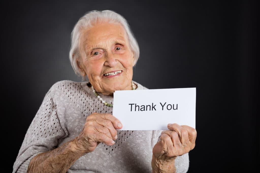 personne âgée avec une pancarte merci
