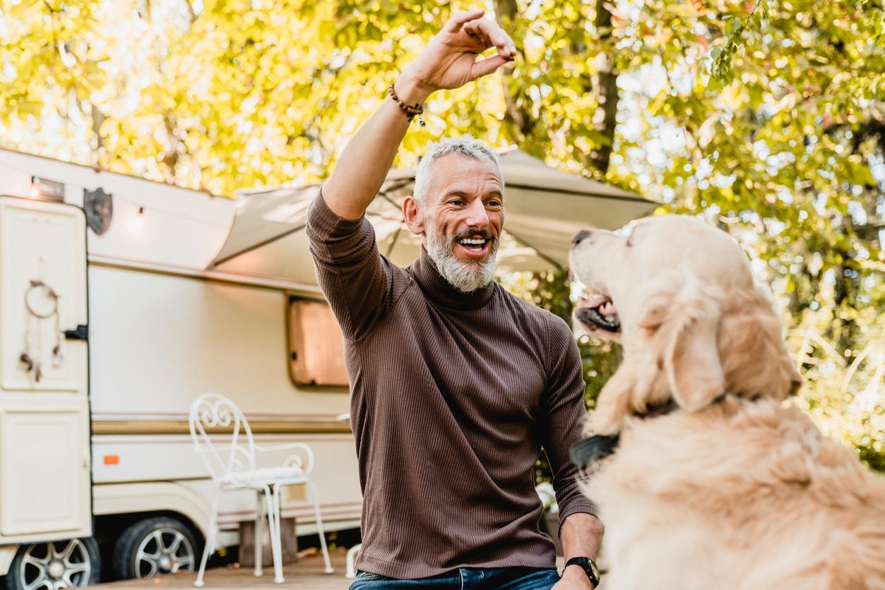 homme qui tend une friandise à son chien