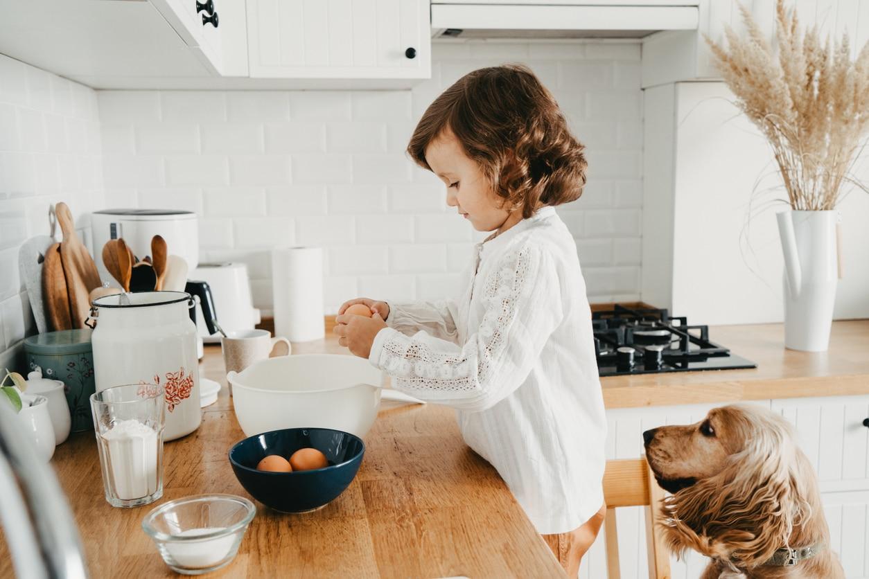 petite fille qui casse des oeufs avec son chien