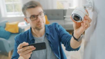 Homme en train d'installer une caméra chez lui