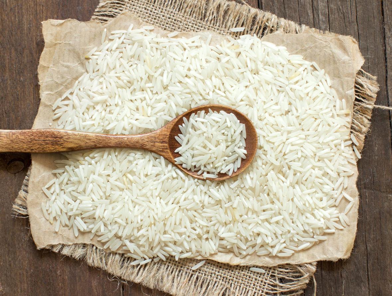 Grains de riz dans une cuillère en bois