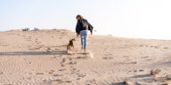 Chien qui court dans le sable à côté de sa maîtresse
